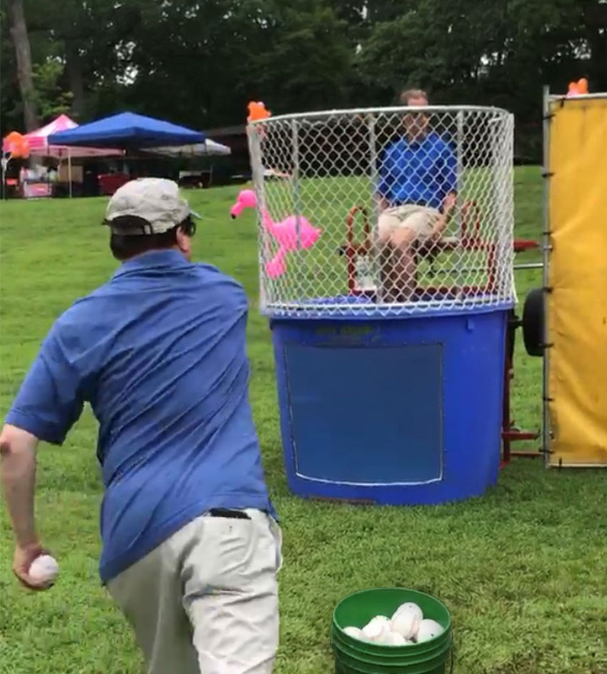 A photo of Ed Wolak, President of the Wolak Group throwing a strike at the dunk tank target.