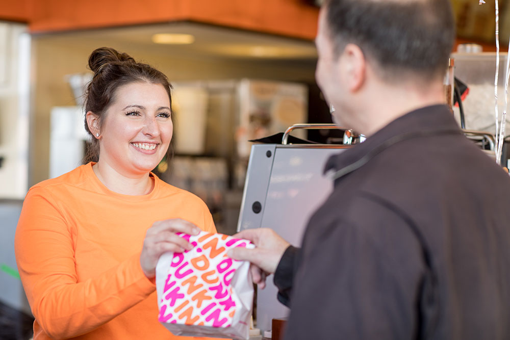 A smiling server at a Wolak Group Dunkin' Restaurant